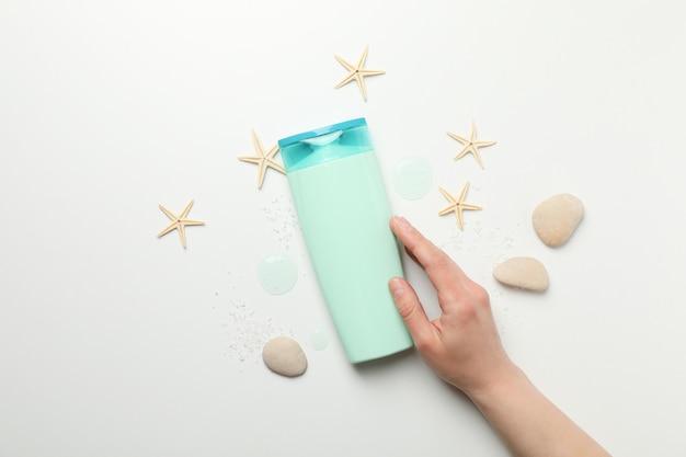 Main féminine touche une bouteille de shampoing sur fond blanc