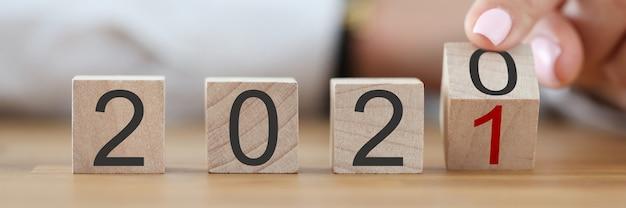 La main féminine transforme le numéro 2020 en numéro 2021 avec son doigt.