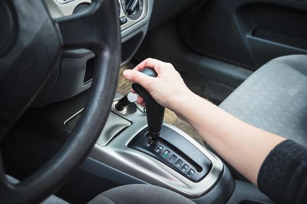Main féminine sur la transmission automatique du levier de vitesses.