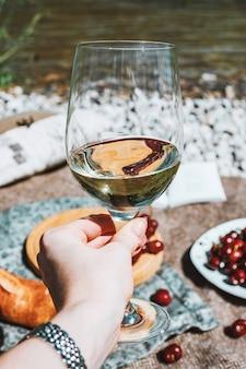 Main féminine avec verre de vin blanc sur la côte de la rivière et fond de pique-nique romantique