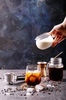 Main féminine verser de la crème dans du café glacé sur un mur bleu avec des grains de café et des glaçons autour de