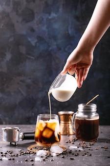 Main féminine verser de la crème dans du café glacé sur une surface bleue avec des grains de café et des glaçons autour de