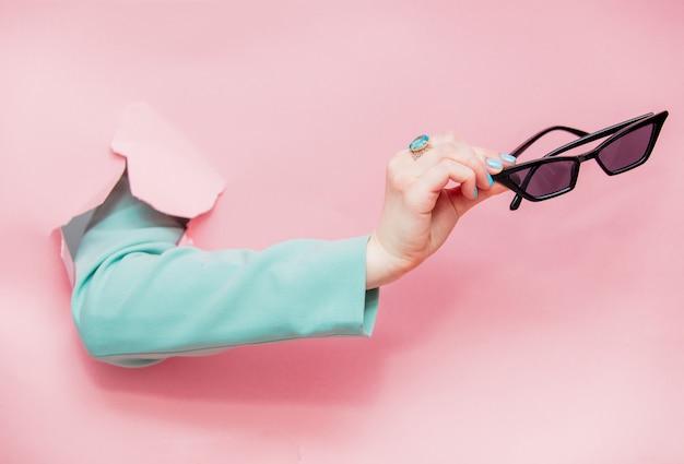 Main féminine en veste bleue classique avec des lunettes de soleil