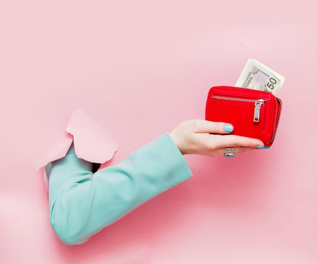 Une main féminine en veste bleue classique montre des dollars dans un sac à main