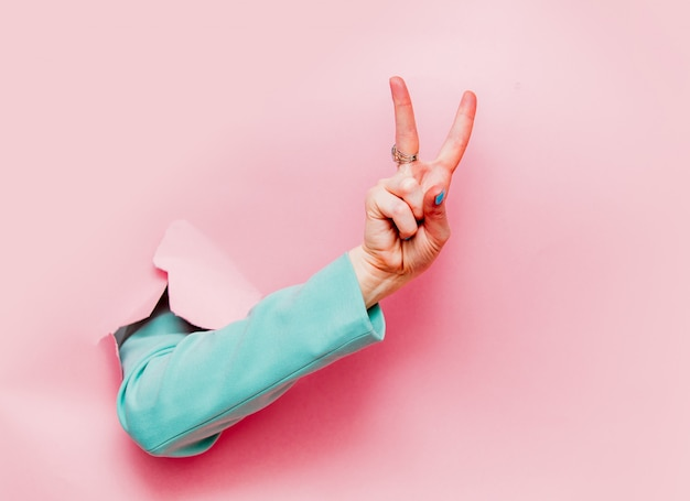 Main féminine en veste bleue classique montre le symbole ok