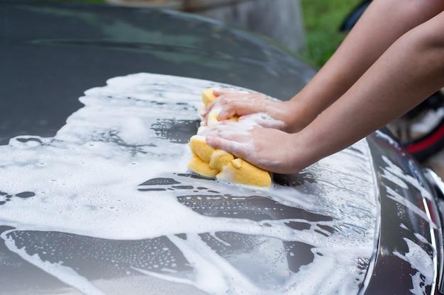 Main féminine avec voiture de lavage en éponge jaune