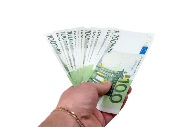 La main féminine vous donne des factures de 100 euros, isolé sur blanc