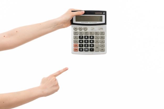 Une main féminine vue de face tenant la calculatrice sur le blanc