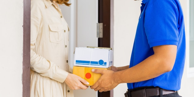 Main de femme acceptant une livraison de boîtes de livreur en uniforme bleu à la porte.