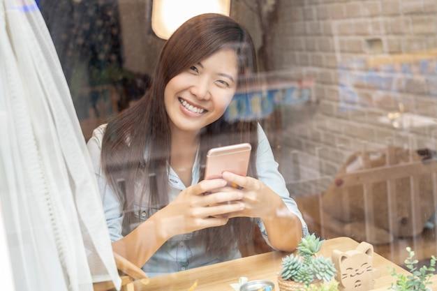 Main de femme d'affaires asiatique à l'aide du téléphone mobile intelligent avec action de bonheur