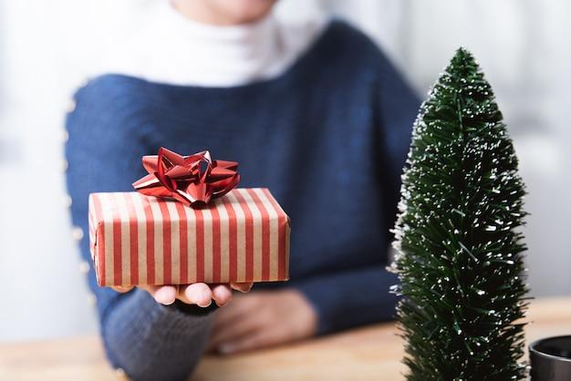Main de femme d'affaires sur la boîte-cadeau en vacances de noël au bureau avec décoration de noël
