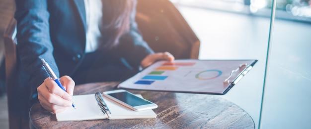 Main de femme d'affaires écrit sur un bloc-notes et à l'aide de tableaux et graphiques d'analyse