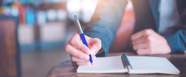 Main de femme d'affaires écrit sur un bloc-notes avec un stylo au bureau.