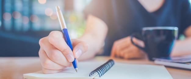 Main de femme d'affaires écrit sur un bloc-notes avec un stylo.