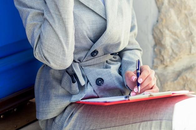 Main de femme d'affaires écrit le document