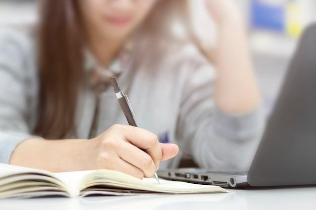 Main de femme d'affaires écrit sur un livre dans le bureau