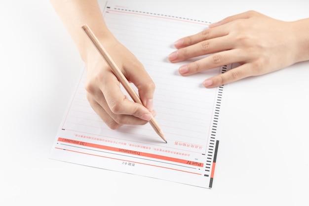 Main de femme d'affaires écrivant sur papier au bureau