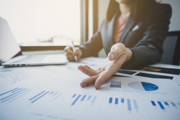 Main de femme d'affaires pointant et analyse le graphique avec calculatrice et ordinateur portable au bureau à domicile