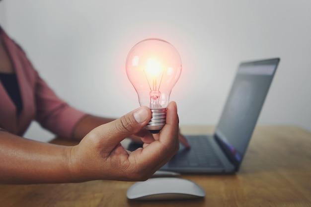 Main de femme d'affaires tenant l'ampoule à l'aide d'ordinateur portable au bureau.