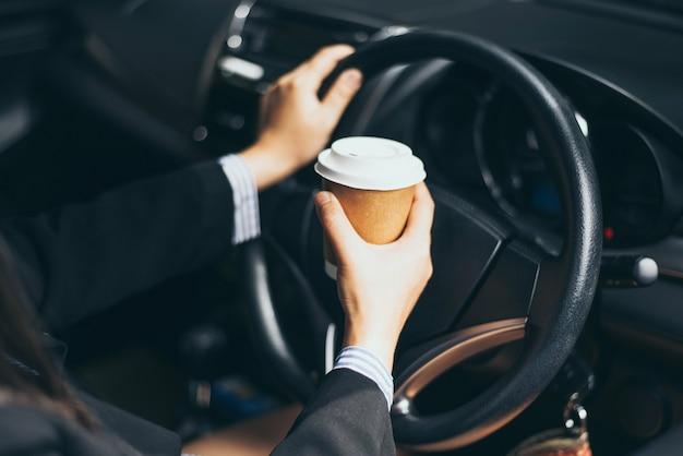 Main de femme d'affaires tenant une tasse de café à emporter, elle conduit le matin.