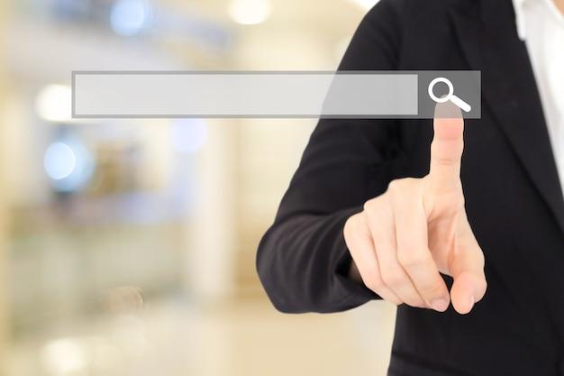 Main de femme d'affaires touchant barre de recherche vide sur arrière-plan flou