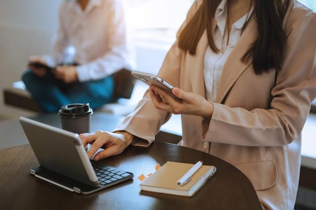 Main de femme d'affaires travaillant avec un nouveau smartphone moderne, un ordinateur et écrivant sur le diagramme de stratégie du bloc-notes comme concept lumière du matin