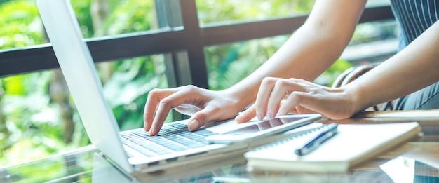 Main de femme d'affaires travaillant avec un ordinateur portable au bureau.