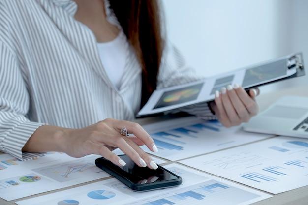 Main de femme d'affaires utilise un smartphone et analyse le graphique avec un ordinateur portable au bureau pour définir des objectifs commerciaux ambitieux et planifier pour atteindre le nouvel objectif.