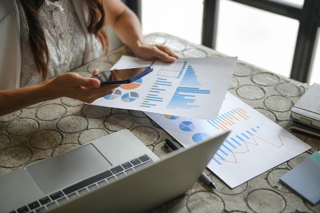 Main d'une femme d'affaires utilise un téléphone mobile pour trouver des informations.