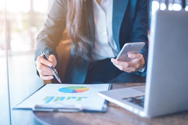 Main de femme d'affaires utilise un téléphone pour travailler sur des graphiques et des graphiques qui montrent les résultats.
