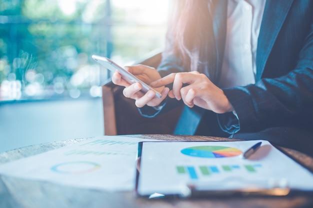 Main de femme d'affaires utilisent un smartphone