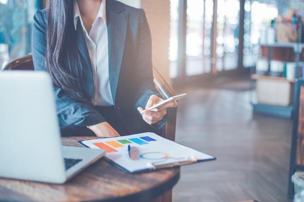 Main de femme d'affaires utilisent des téléphones portables et travaillent sur des graphiques et des graphiques