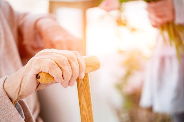 Main de femme âgée avec canne à la lumière