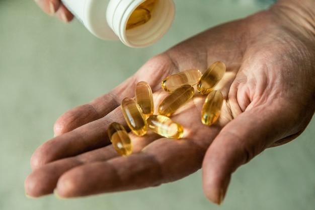 Main d'une femme âgée avec des pilules