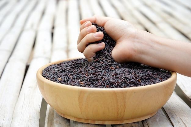 Une main de femme d'agriculteur a ramassé le riceberry du bol en bois plein de riceberry ci-dessous le concept d'un mode de vie sain