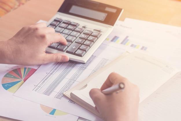 Main de femme à l'aide de la calculatrice et de l'écriture prendre note avec calculer