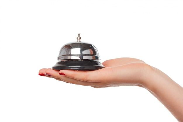 Main d'une femme à l'aide d'une cloche d'hôtel isolée