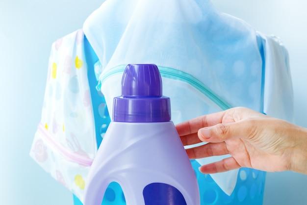 Main de femme à l'aide d'un détergent liquide pour laver le linge