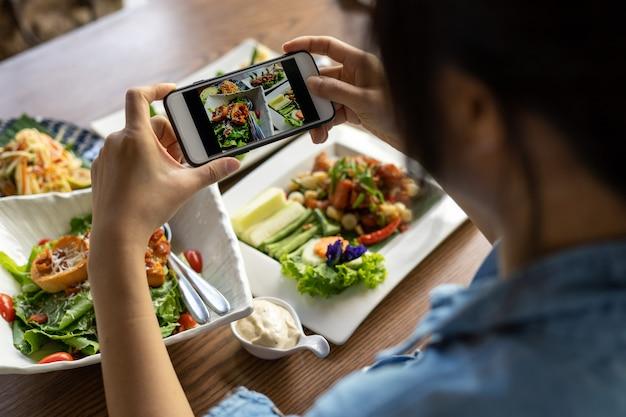 La main d'une femme à l'aide d'un smartphone pour photographier le déjeuner ou le dîner dans un restaurant.