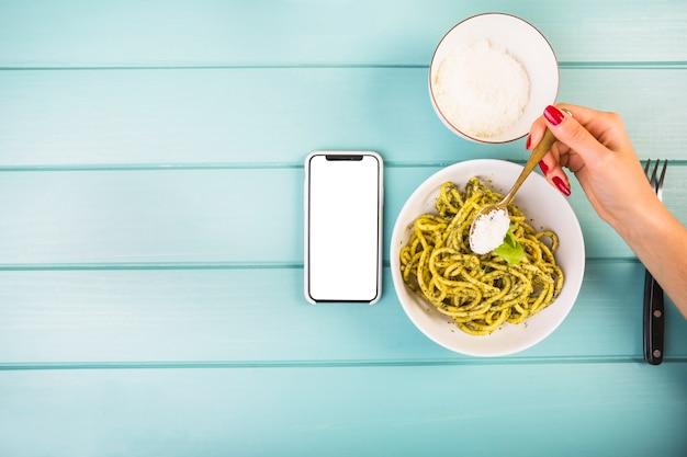 Main de femme ajoutant l'assaisonnement sur les spaghettis