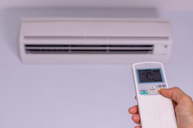 Main femme allumant le climatiseur. concept d'économie d'énergie.