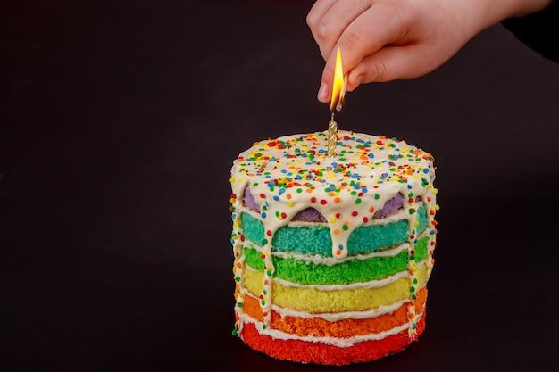 La main de la femme allume une bougie sur le gâteau d'anniversaire.