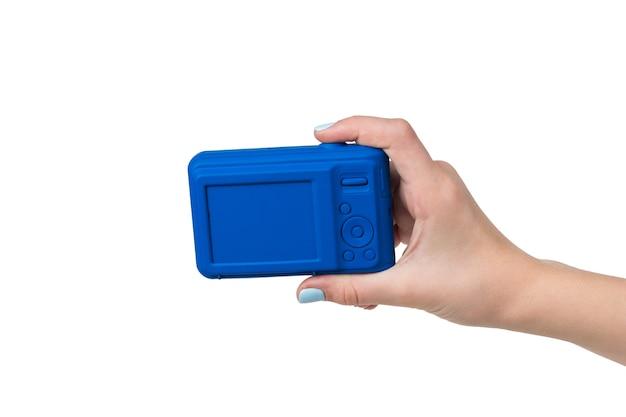 La main d'une femme avec un appareil photo bleu isolé sur une surface blanche