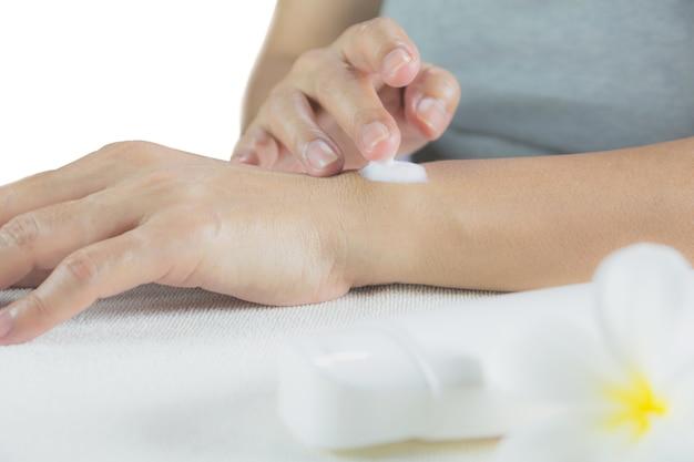 Main de femme appliquer la lotion sur la peau de la main arrière avec une bouteille de lotion