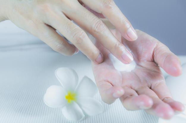 Main de femme appliquer la lotion sur la peau de la main avec une bouteille de lotion sur une table blanche.