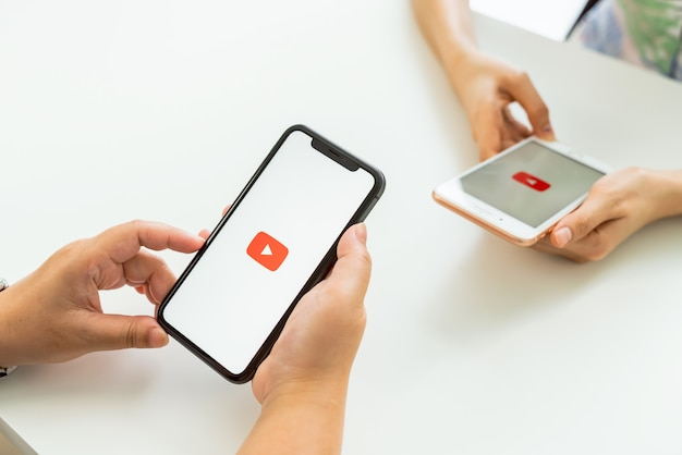 Main de femme appuie sur l'écran affiche les icônes d'application sur le téléphone