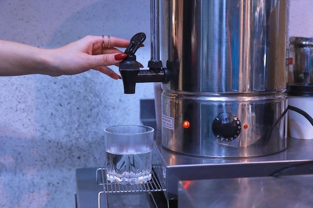 La main d'une femme appuie sur le robinet pour verser l'eau chaude de la chaudière dans un verre transparent sur la table