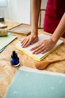 Main de femme en appuyant sur le moule pour faire du papier
