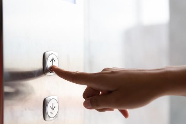 Main de femme appuyer sur un bouton d'ascenseur à l'intérieur du bâtiment