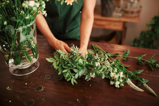 Main de femme arrangeant des plantes dans un vase